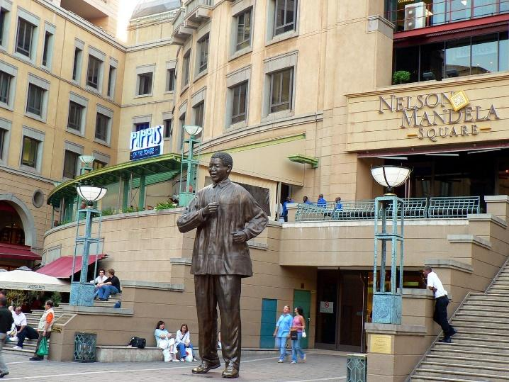 The picture shows the Nelson Mandela Square. A tall, weathered statue of Nelson Mandela stands in the center of the square. People walk or sit around the square. On the right of the picture stairs lead off frame. On the left, more people sit under shade.