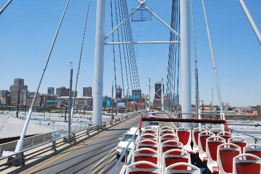 The picture is taken from on top of a double decker bus on a bridge. The supports of the bridge frame the skyline of a large city in the background. The sky is perfectly clear and blue.