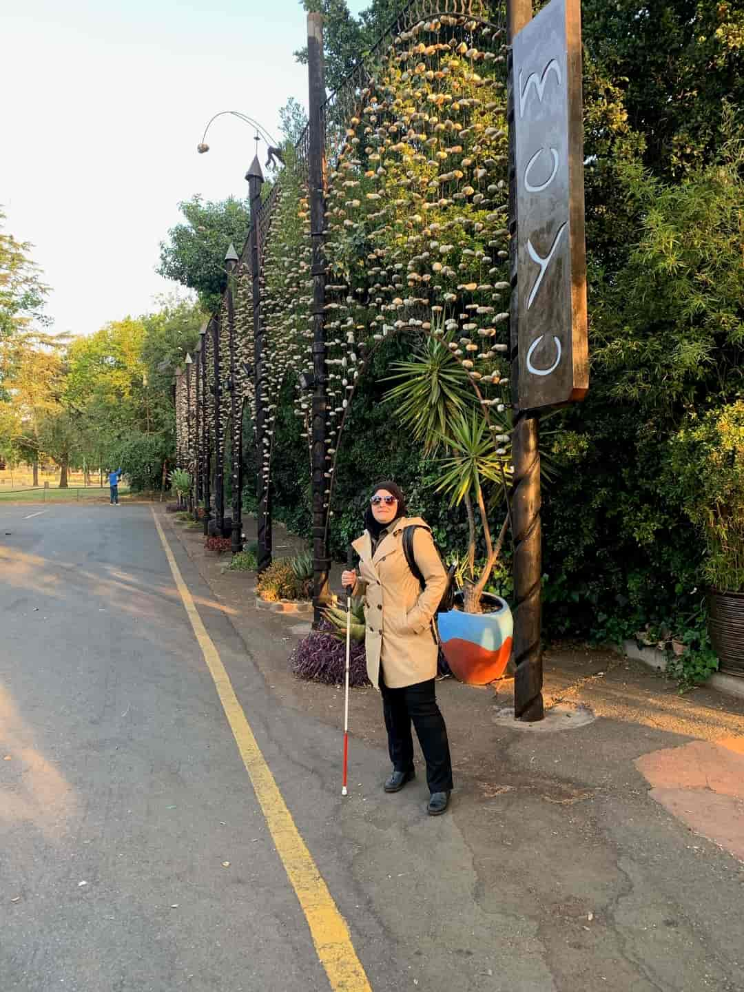 "Mona stands on the side of a road. She wears a tan jacket, black pants, sunglasses, and holds her cane. Behind her is a sign that reads ""Moyo"" and various trees and foliage. Before her is an empty asphalt street."